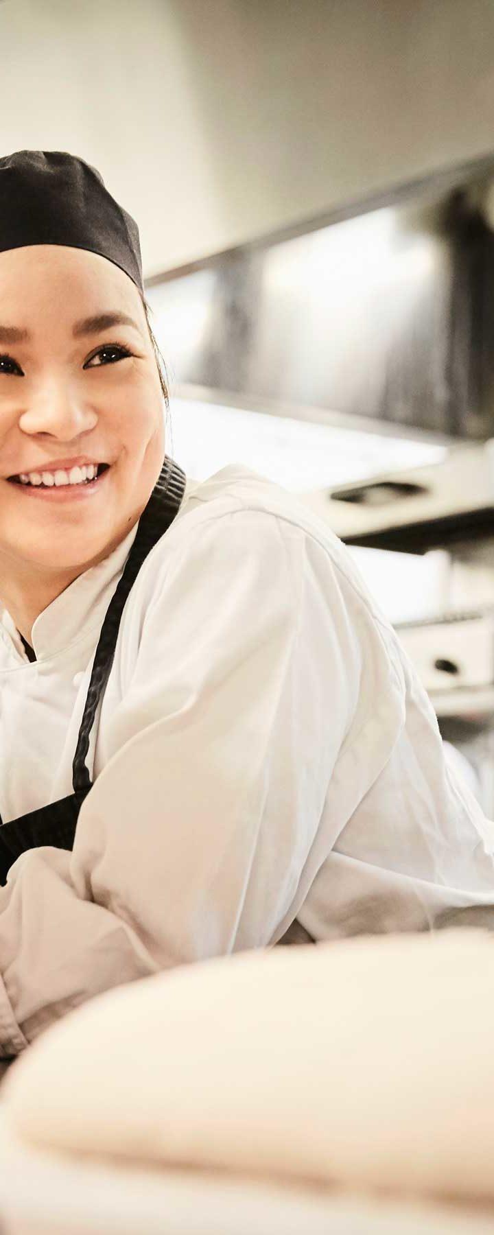 Elev lutar sig på köksbänken med stöd av armbågarna. Hon ler åt sidan.