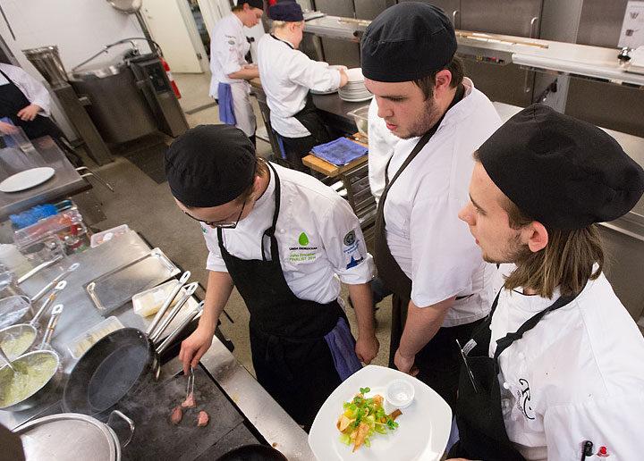 Tre elever står och strängs i köket medan en håller i en tallrik, en står och ser på och den ena steker kött.