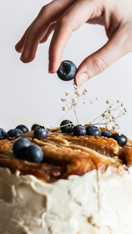 hand lägger blåbär på en tårta