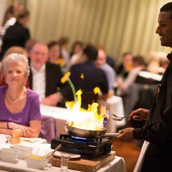 Elev står och lagar mat framför restaurangens gäster. Hans stekpanna eldar i lågor.
