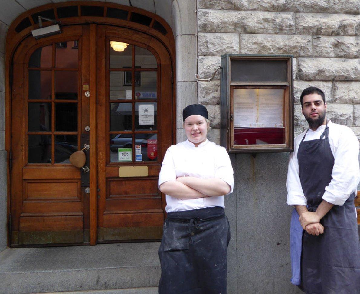 Två elever står utanför ett hotell samt restaurang.