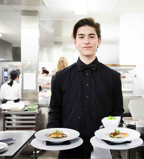 Bild på elev som står i ett kök och håller två tallrikar med maträtter på, därav en dessert också.