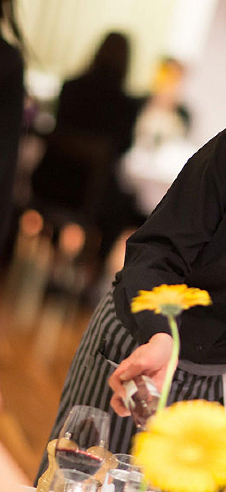 Servitris med svart skjorta och vinröd fluga står och saltar en maträtt.