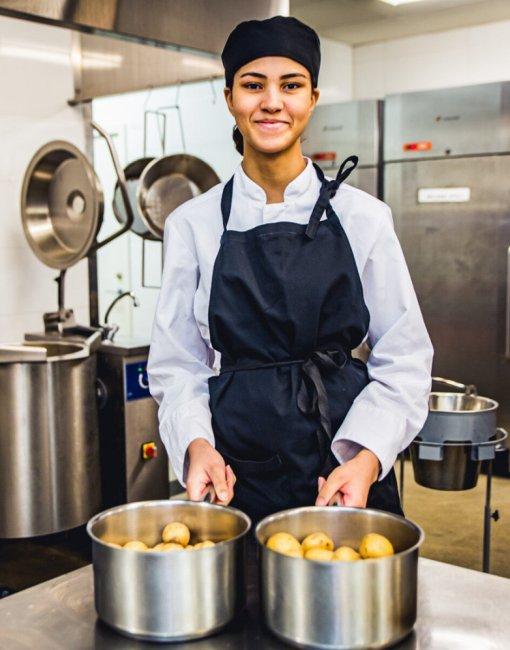 Kock i köket med två kastruller med potatis i