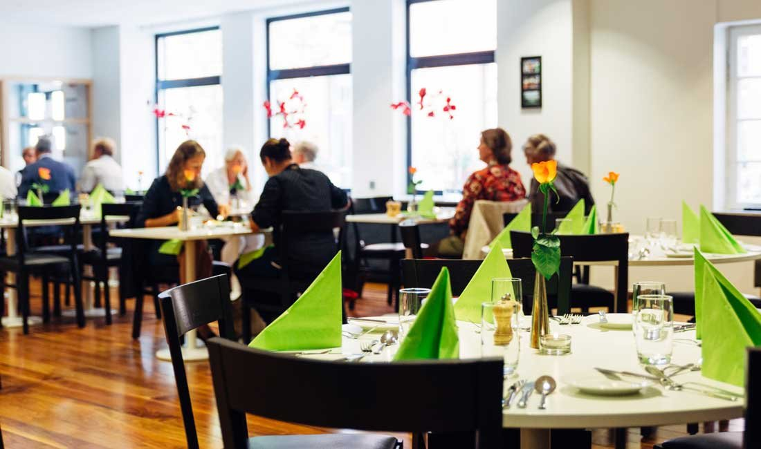 Bild på matsal. På borden är det dukat med tallrik, glas, och gröna servetter.