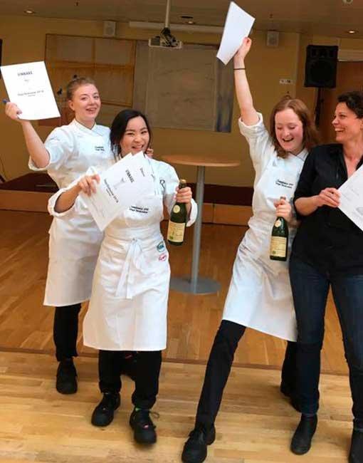 Tre elever från Internationella Hotell- och Restaurangskolan hurrar med pappersdiplom och varsin flaska i handen.